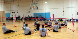 photo of people seated on the gym floor playing volleyball