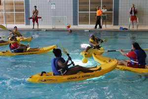 photo of people in kayaks playing a ball game in a swimming pool