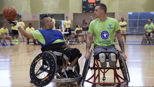 photo of two men in wheelchairs playing basketball