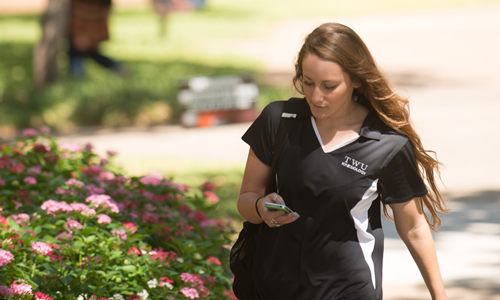 a TWU kinesiology student checking her phone while walking across campus