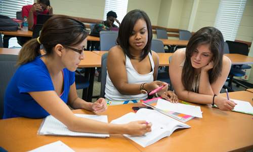 three TWU students studying together