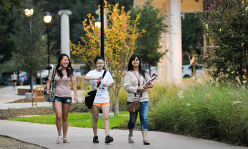 photo of three TWU students strolling past the new Fitness & Recreation Center
