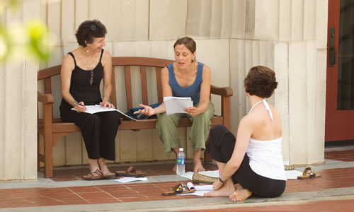 photo of three older than average TWU students studying together on the porch of one of classic buildings on campus
