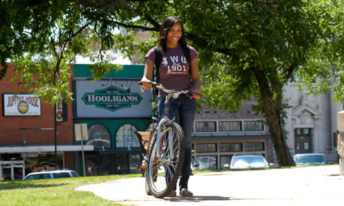 photo of TWU student with her bicycle on the Denton Square