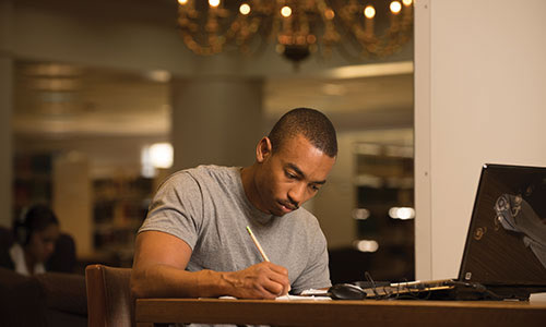 photo of a male student at TWU studying in the library
