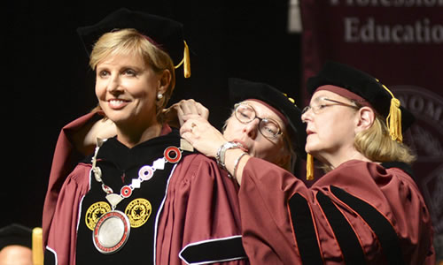 photo of Regents Sue Bancroft and Mary Pincoffs Wilson fastening the President's Medallion around Chancellor Feyten's neck