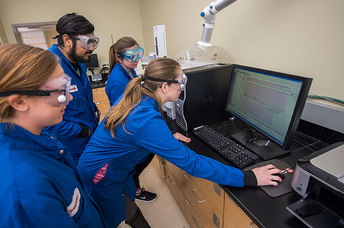 A group of chemistry students in protective goggles and suits study results on a computer monitor