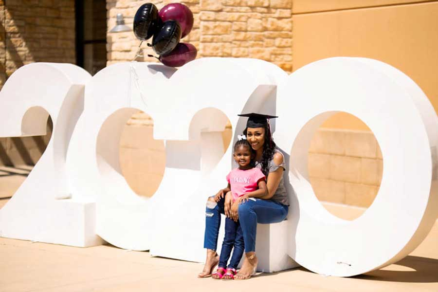 A TWU graduate sits on a large 2020 lettering with her daughter on her lap.