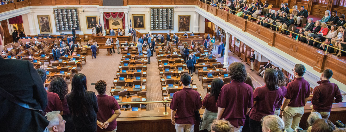 A group of TWU students stand in the seating area at the Texas state capitol