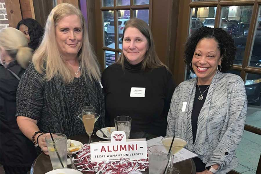 Three TWU alumni enjoy drinks at a table during an alumni event.