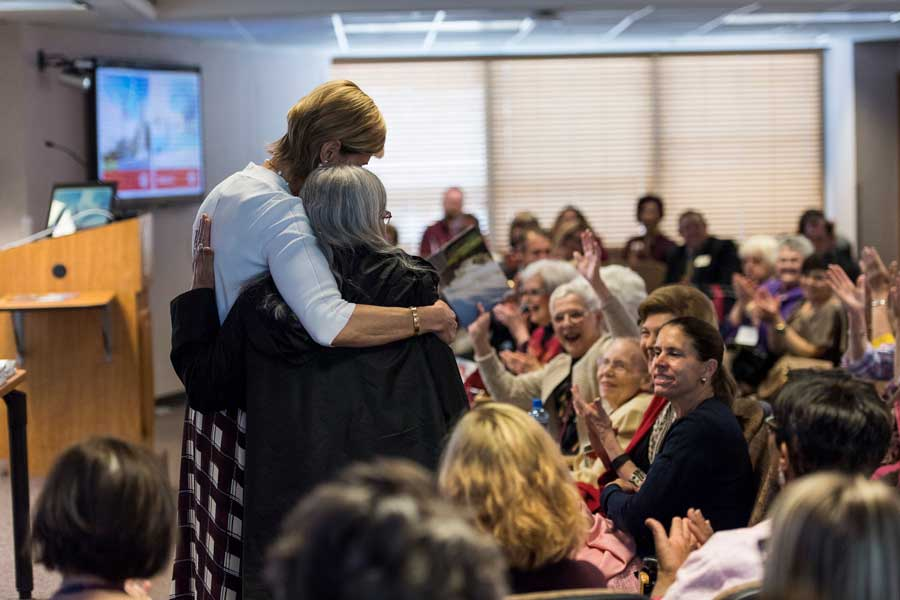 Chancellor Feyten hugs an alum during an awards ceremony.
