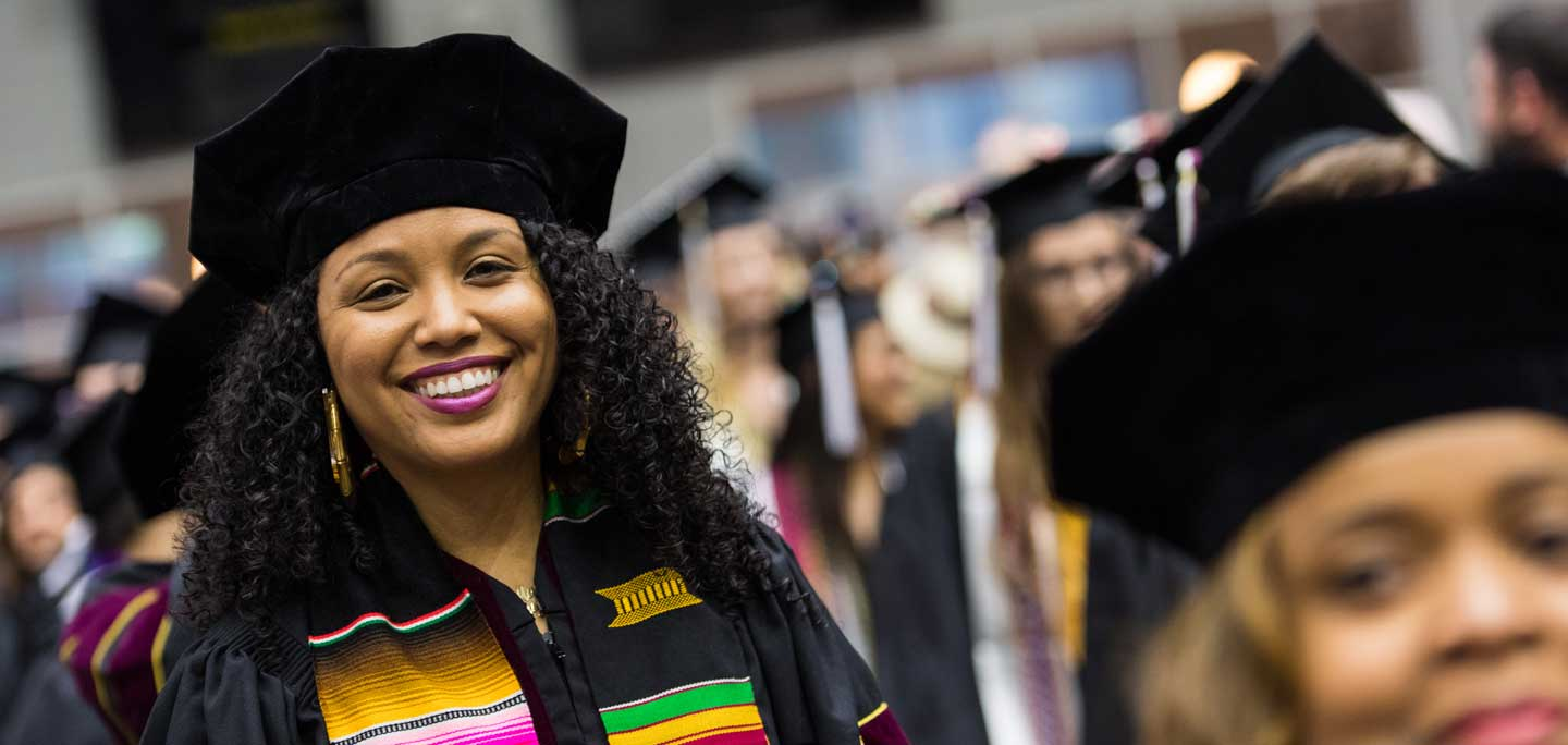 A TWU doctoral student in academic regalia during a commencement ceremony.