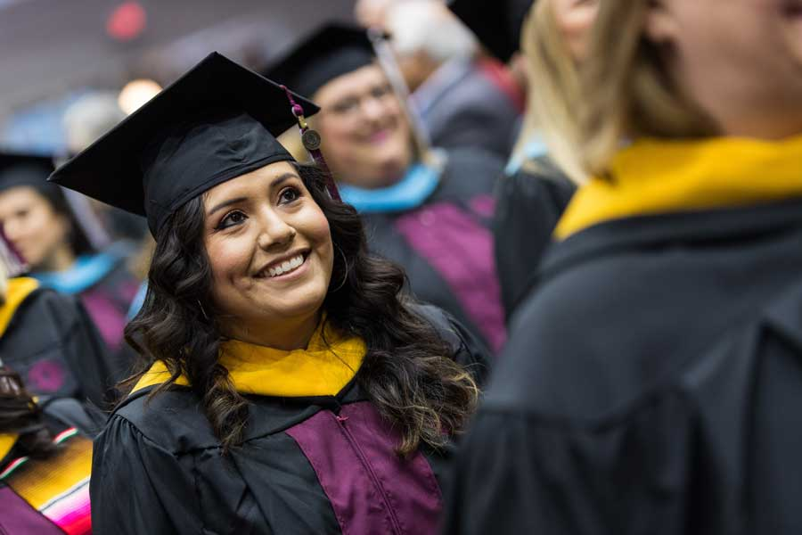 A woman smiles in academic regalia during a TWU commencement ceremony.