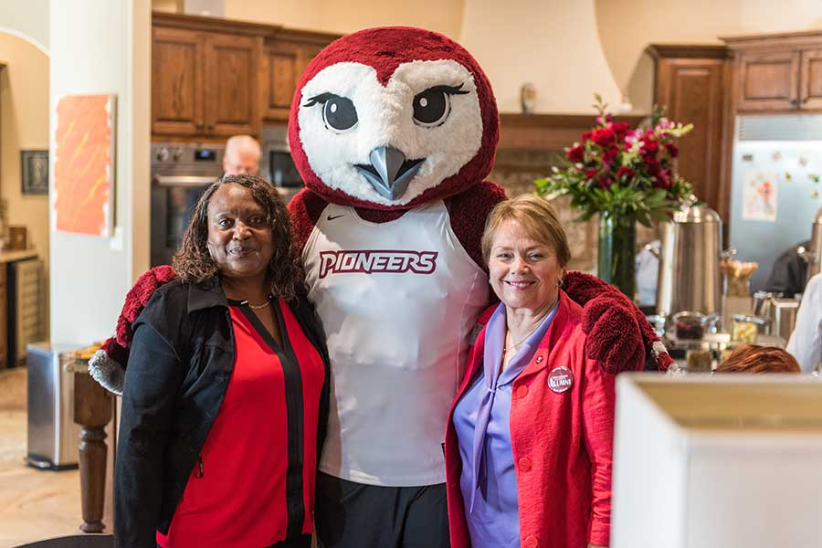 Oakley hugs two alumni during an event at Chancellor Feyten's house.