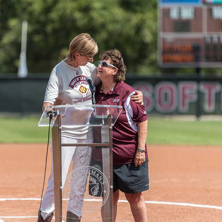 Dianne Baker and TWU Chancellor Carine Feyten hug on the new softball field on TWU's Denton campus.