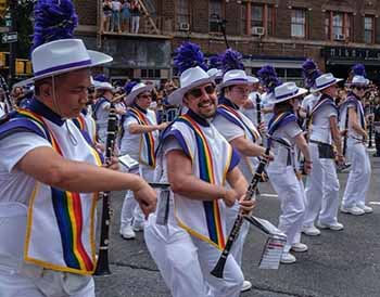 Louis Rendon marching with the band wearing a pride sash.
