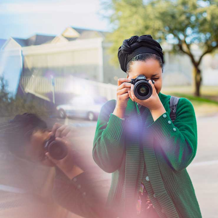 Nitashia Johnson holding a camera and taking a photo of herself with a creative reflection of her to the left.