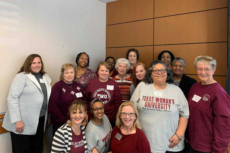 A group of TWU alumni smile for a group photo.