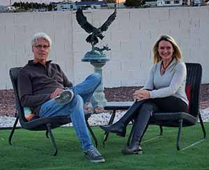 Jody and David Popple sitting by a sculpture