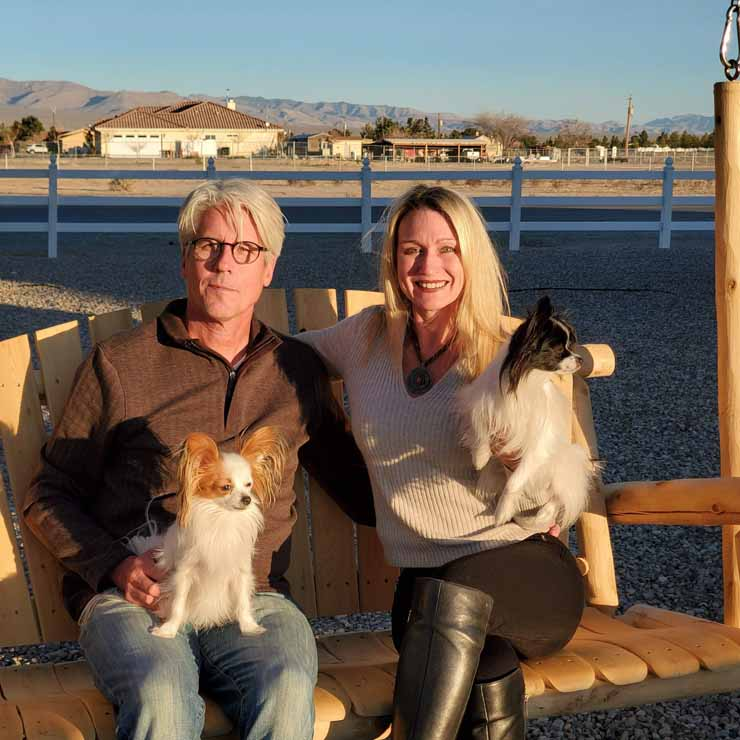 Jody and David Popple sitting on a swing with 2 Papillon breed dogs.