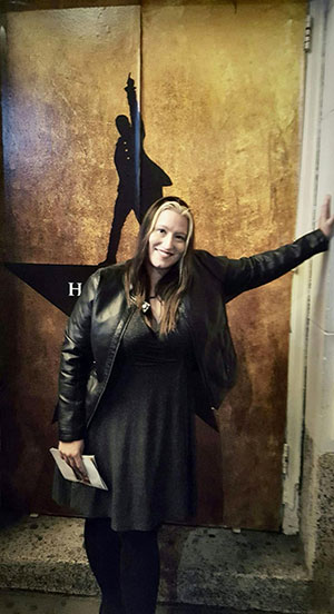 Lacy Brown stands in front of a doorway with the Hamilton Broadway poster on it