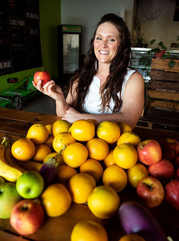 Loni Puckett stands in front of a large bowl of fresh fruit, holding an apple in her hand.