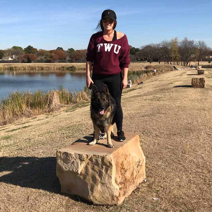 Loni Puckett stands outside on top of a large stone with a German Shepherd dog.