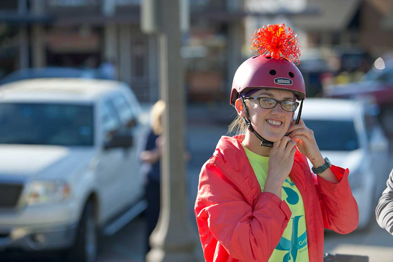 A student putting on her helmet at the Denton downtown square during the ARTSWALK 2016 bike parade