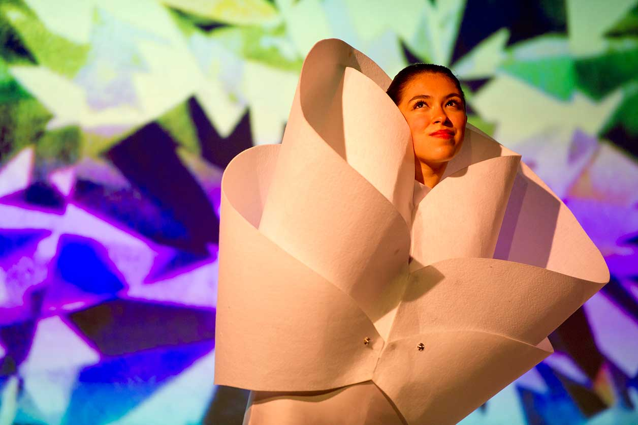 a student dance performer's head comes out of a giant flower costume