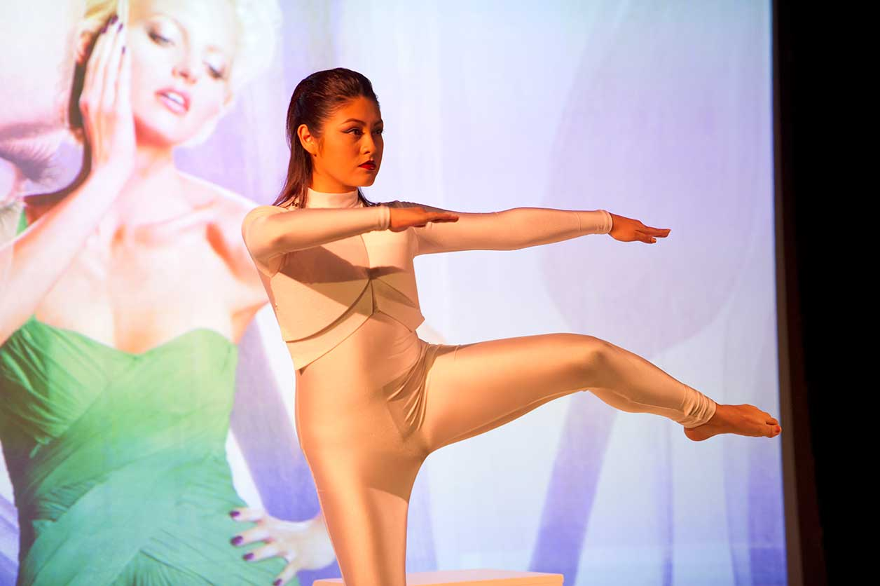 a dance student balances on one leg as she performs