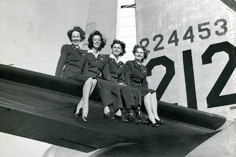 Four Women Air Force Service Pilots (WASPs) sit on the wing of a fighter aircraft