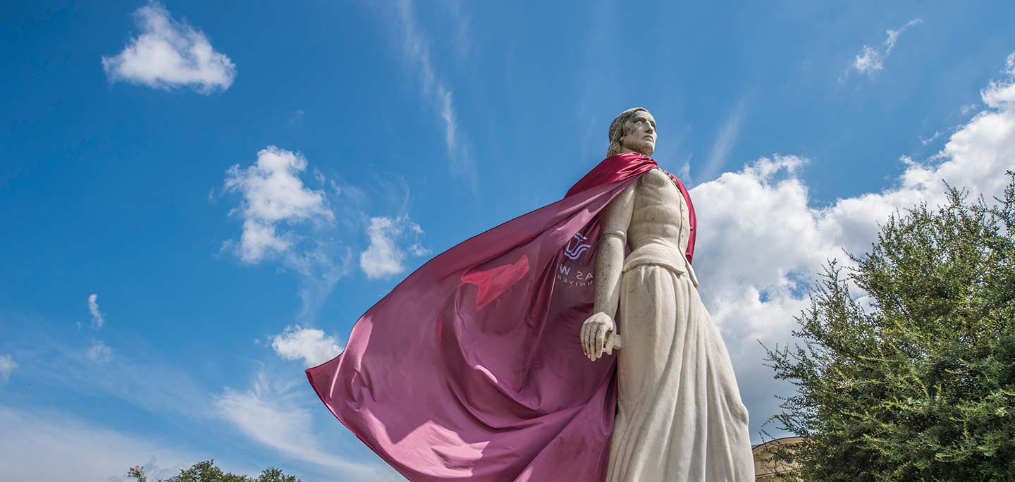 The Pioneer Woman statue wearing a maroon cape that flutters in the wind