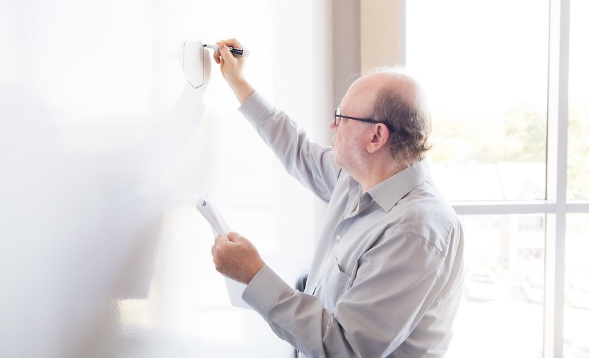 Michael Bergel draws structure for his patented anti-cancer compounds on a whiteboard.