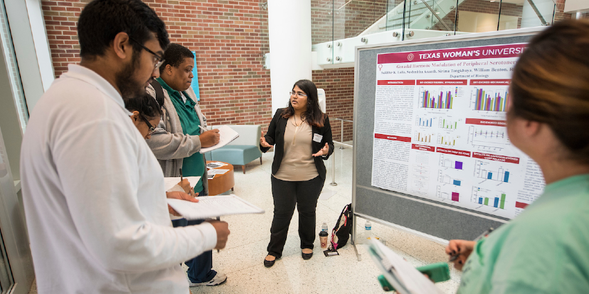TWU biology student presenting her research poster to a crowd in ASSC.