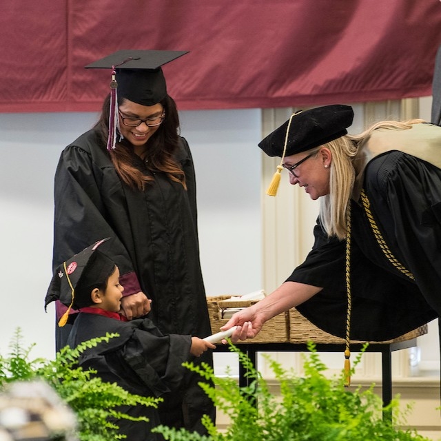 A woman hands a diploma scroll to a little boy wearing a graduation cap and gown as his mother, also in a graduation cap and gown, smiles down at him