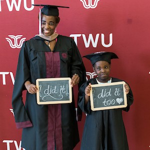 A young woman and her little boy both stand wearing matching graduation caps and gowns, holding signs that read 'I did it' and 'I did it too'