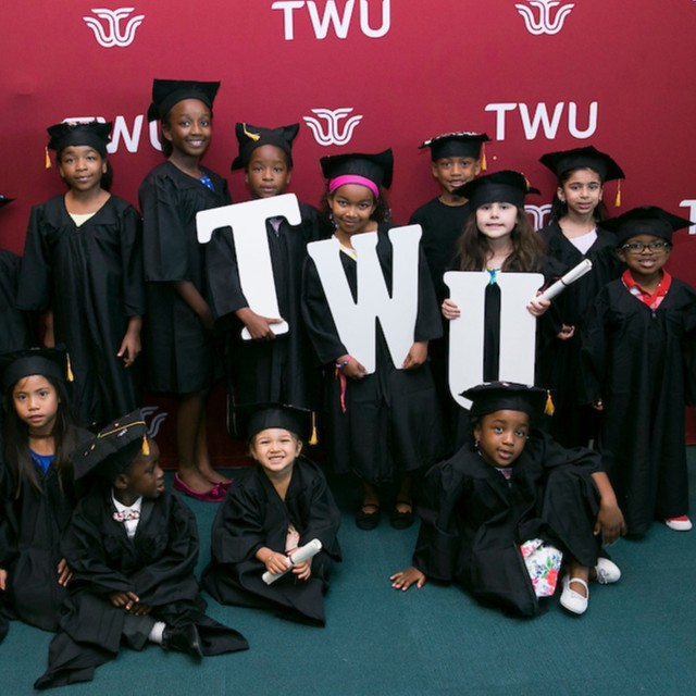 A group of kids wearing graduation caps and gowns pose around giant white letters TWU
