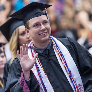 A young man in graduation cap and gown wearing special veteran cords waves at family and friends