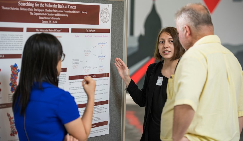 Chem/Biochem student Claudette Fraire presents her research poster to two guests at Golden Triangle Mall