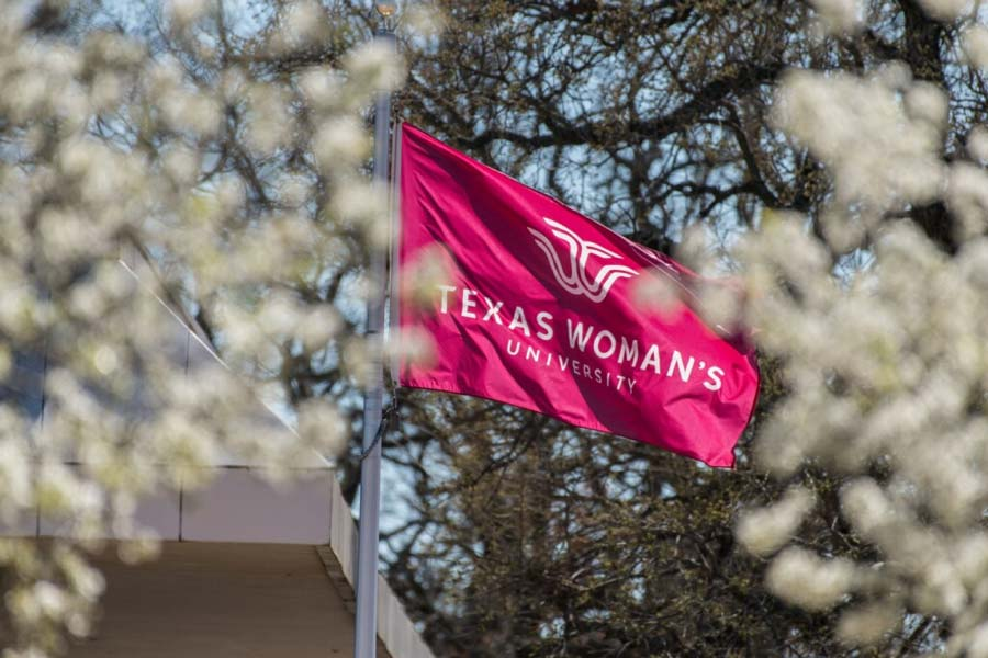 The TWU flag flutters in the breeze among the Denton campus' redbud blooms
