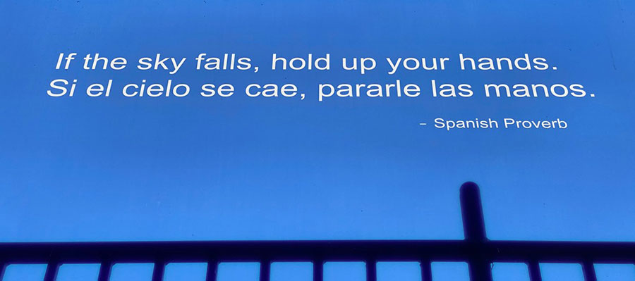 Text reads 'If the sky falls, hold up your hands' then repeats the phrase in Spanish