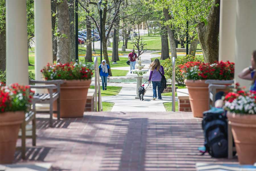 students walk along the wide sidewalk which runs past the Denton campus student union building