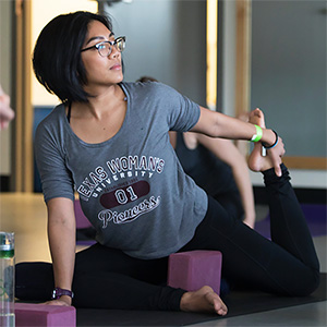 A young woman wearing a gray TWU t-shirt stretches during a workout session