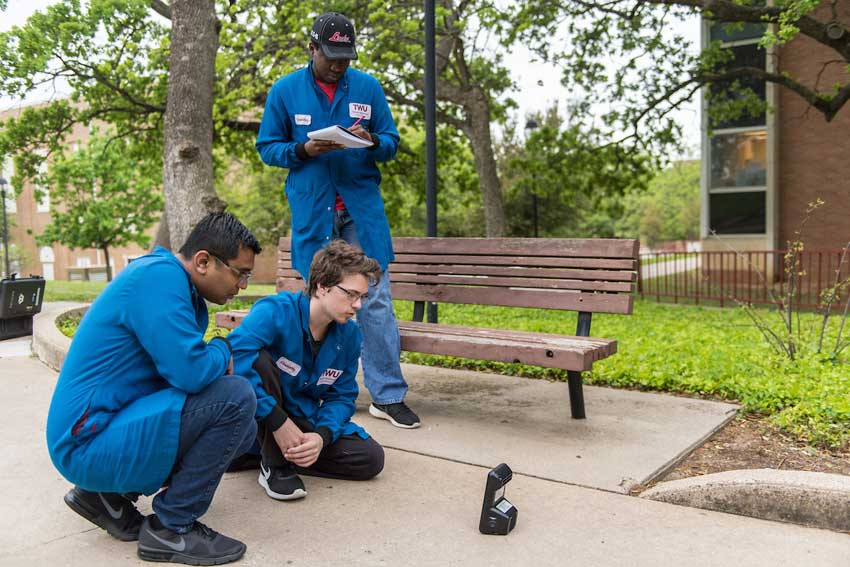 Environmental chemistry students Akinwande Akinniyi, Trent Kyrk and Ashik Patel test air quality outside of the CFO building on TWU's Denton campus.