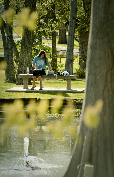 Student studying near the pond