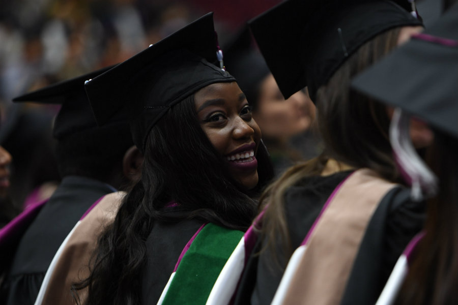 A graduate smiling at her commencement ceremony.