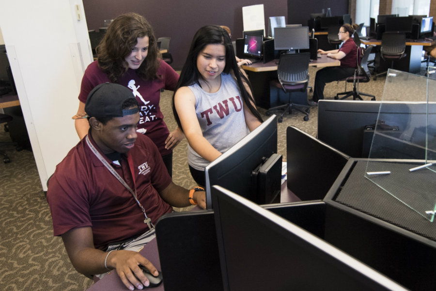 Three students working together in a computer lab setting.