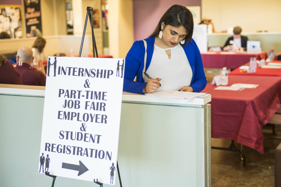 A woman filling out an application at the Internship and Part-Time Job Fair.