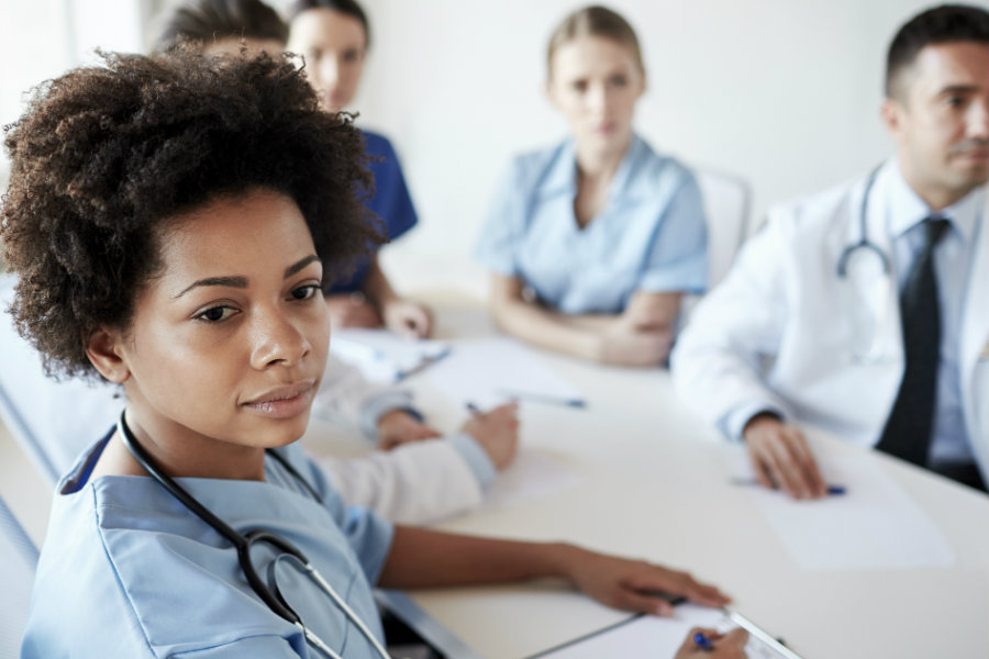 A woman in scrubs sitting in a meeting with other nurses.