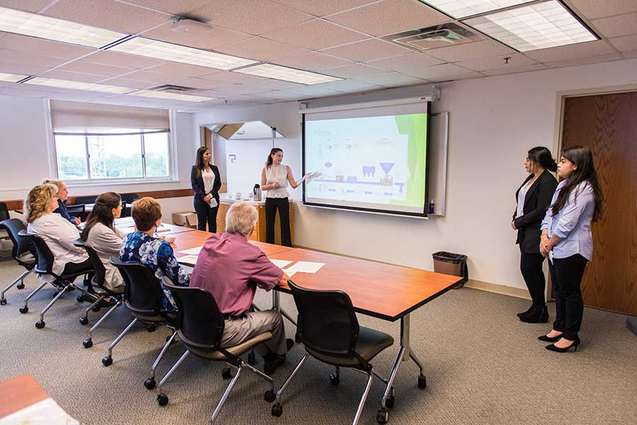 Three TWU female students in professional dress giving a presentation in a classroom setting.
